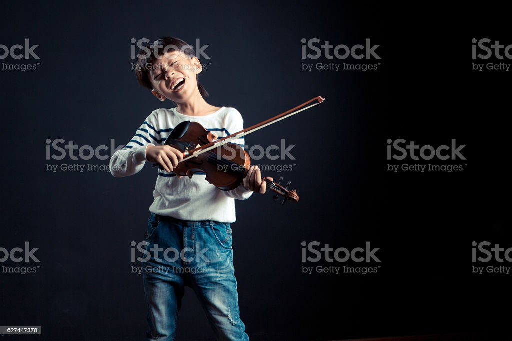boy playing a Violin isolated over a black background stock photo