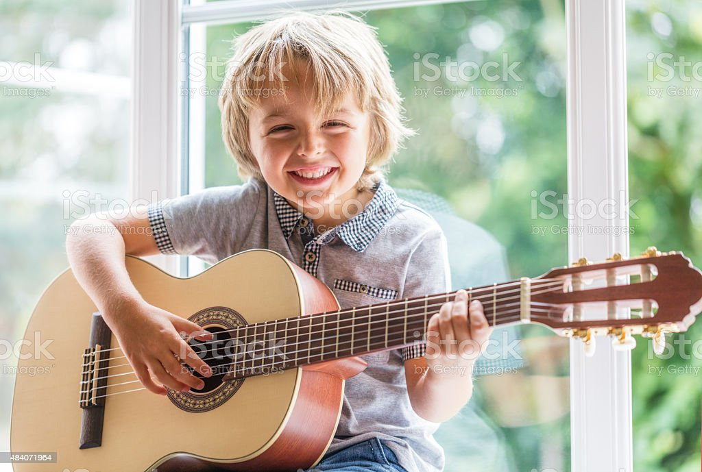 Boy playing acoustic guitar stock photo