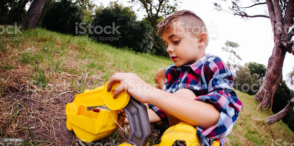 Boy playing and digging with toy excavator in garden stock photo