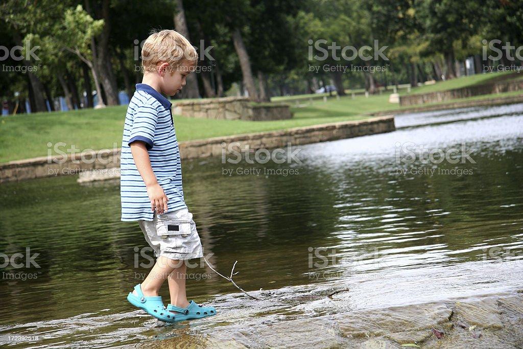 Boy playing at a river royalty-free stock photo