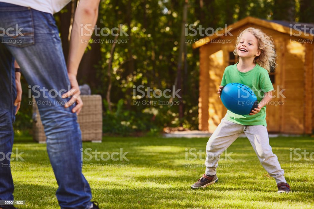 Boy playing ball with father stock photo