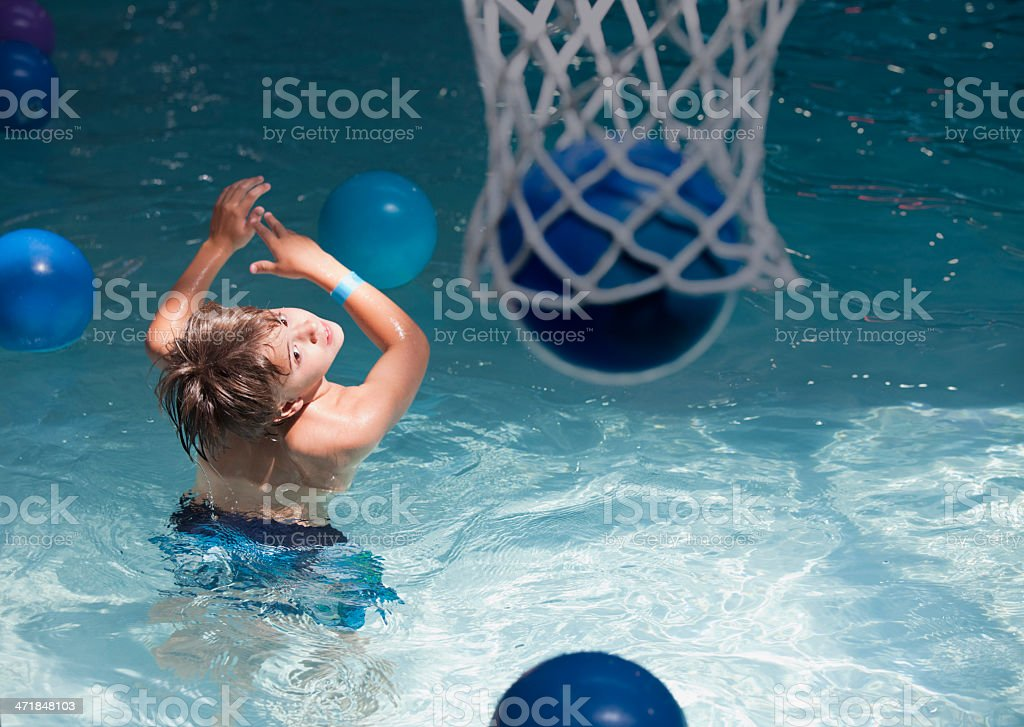 Boy playing basketball at the indoor water park stock photo