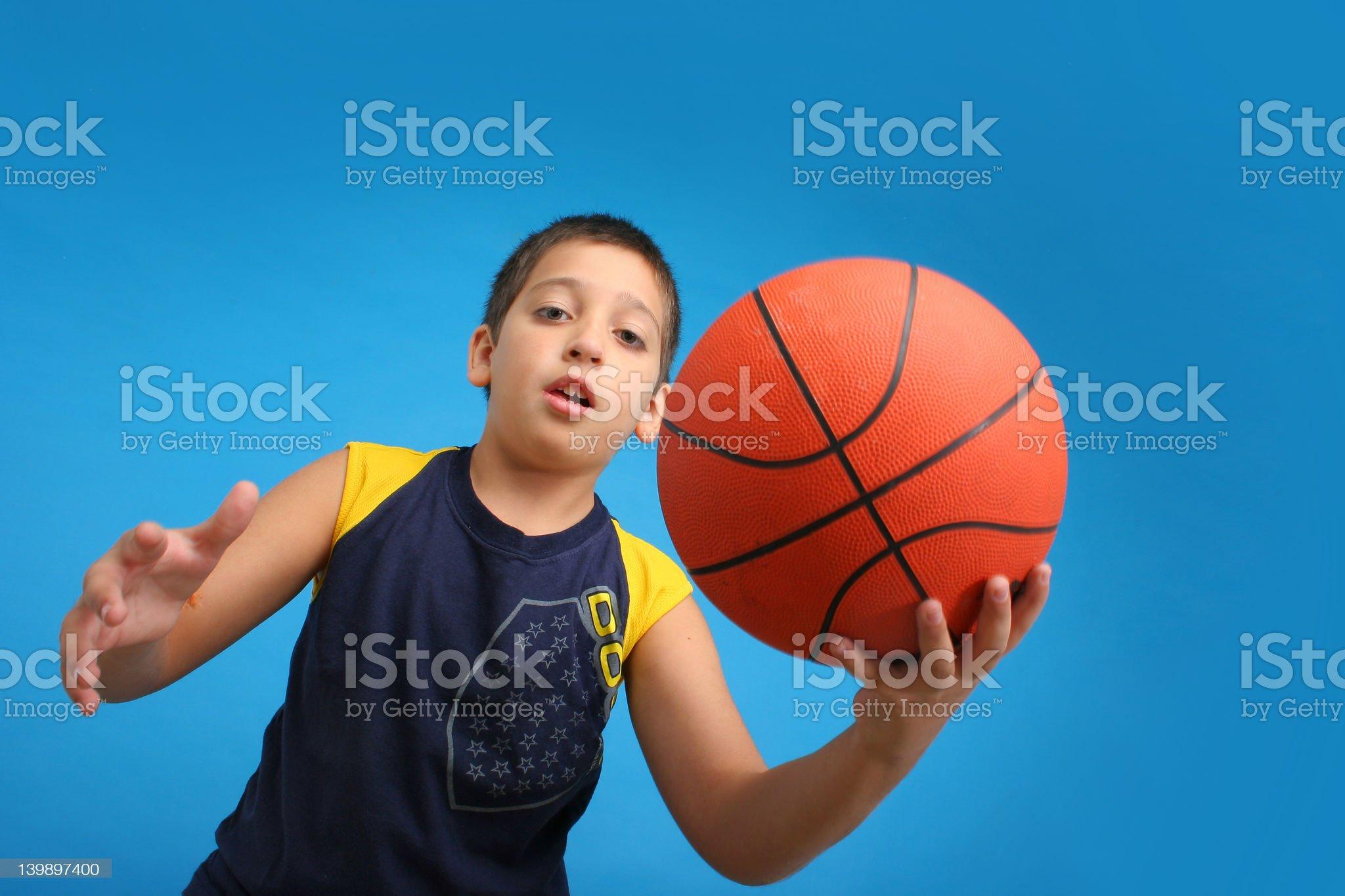 Boy playing basketball. Blue background royalty-free stock photo