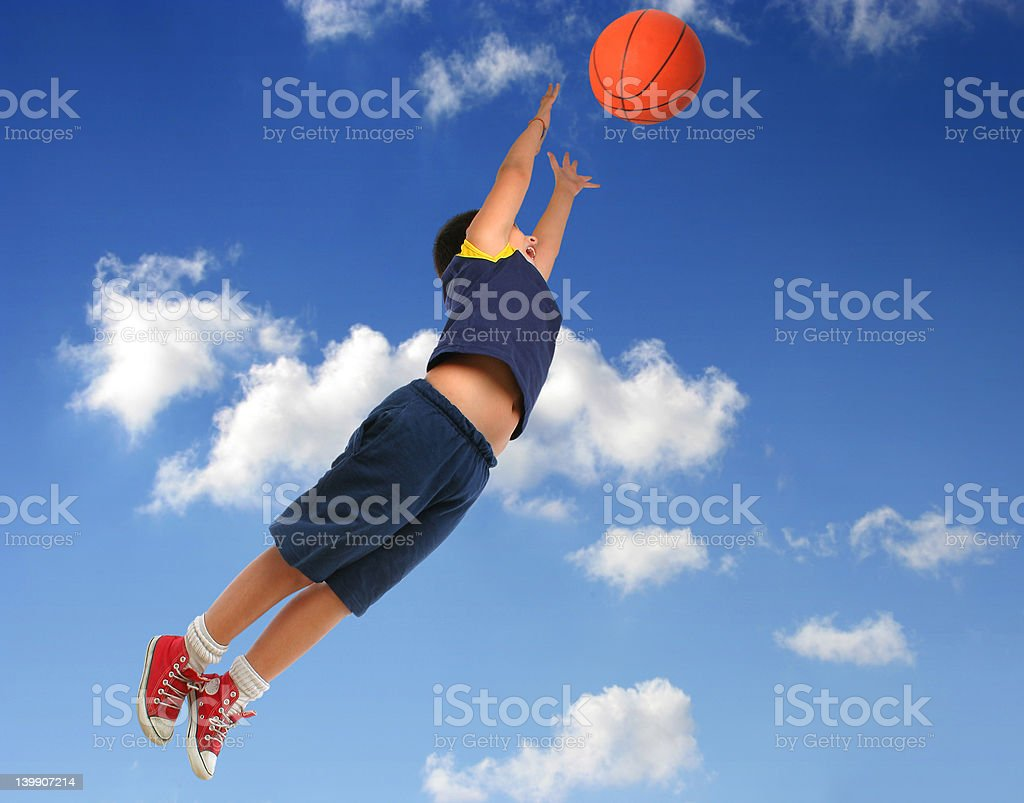 Boy playing basketball. Flying with blue sky stock photo