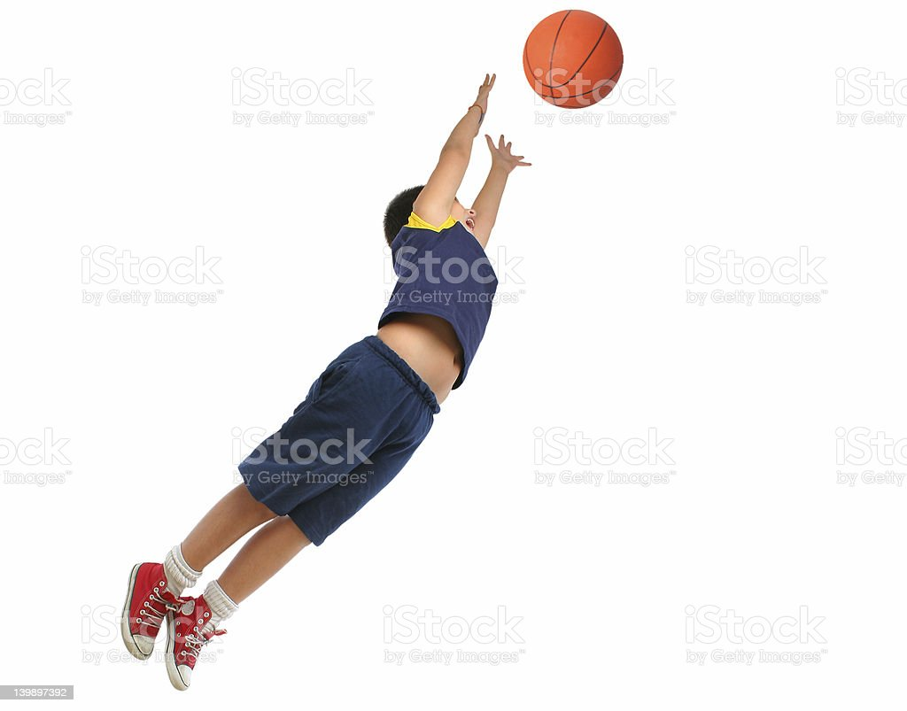 Boy playing basketball isolated. Flying and jumping stock photo