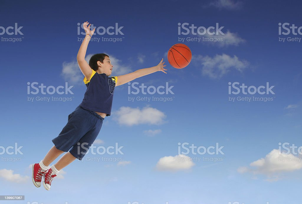 Boy playing basketball jumping and flying stock photo