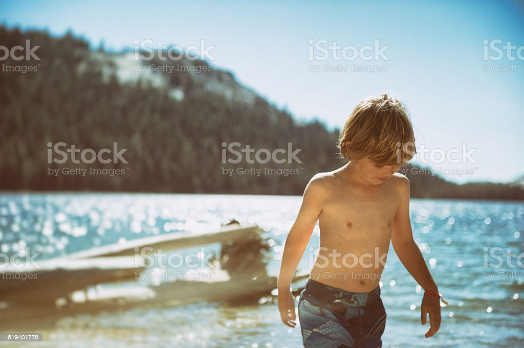 Boy playing by a lake in late afternoon in Yosemite stock photo