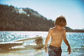 Boy playing by a lake in late afternoon in Yosemite