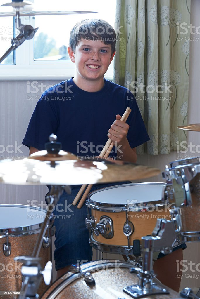 Boy Playing Drum Kit At Home stock photo
