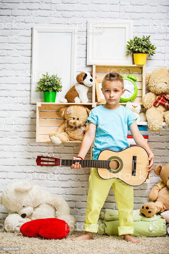 Boy playing guitar in his room stock photo