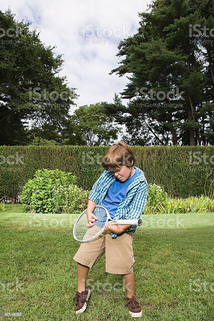 Boy playing guitar on a tennis racket stock photo