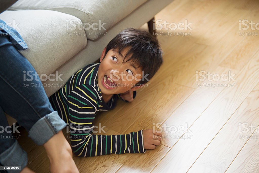 Boy playing hiding in the sofa stock photo