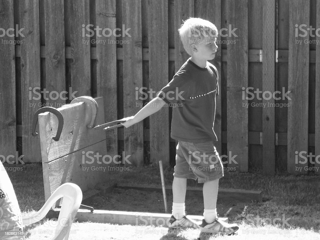 Boy playing horseshoes royalty-free stock photo