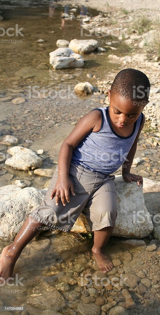 Boy Playing in a Creek stock photo