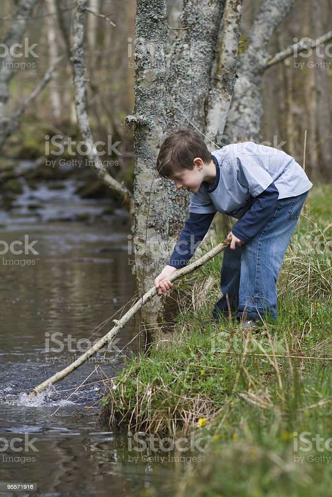 Boy playing in a stream royalty-free stock photo