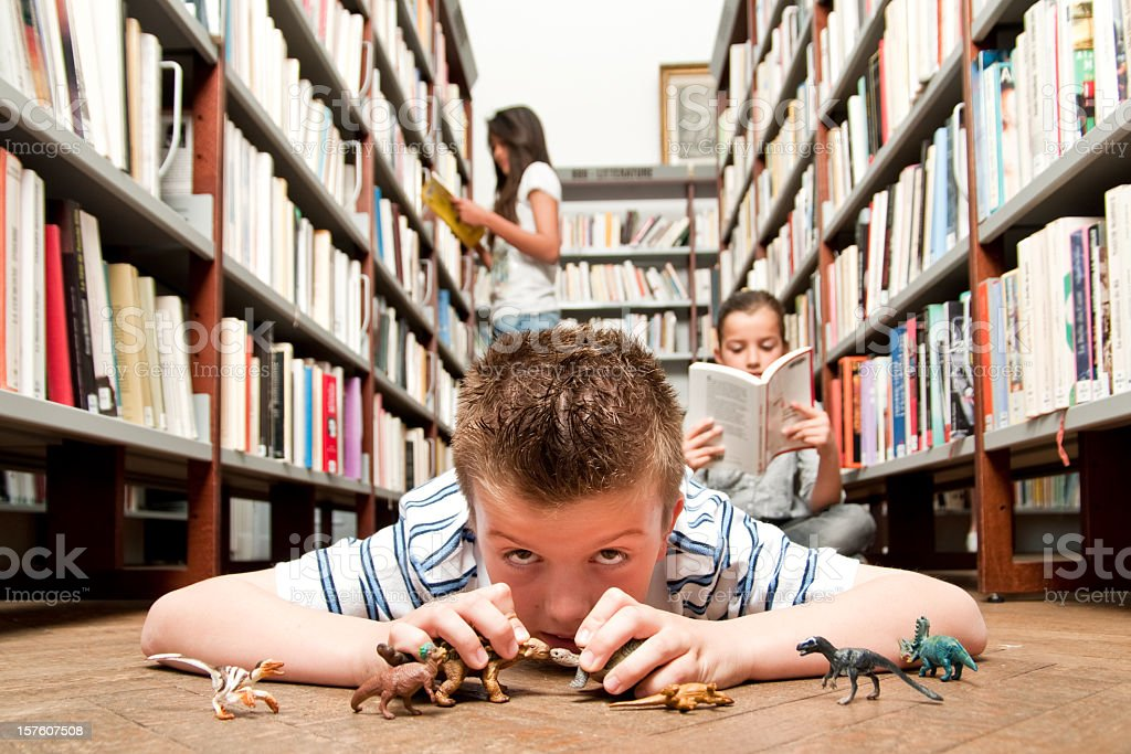 Boy playing in library royalty-free stock photo
