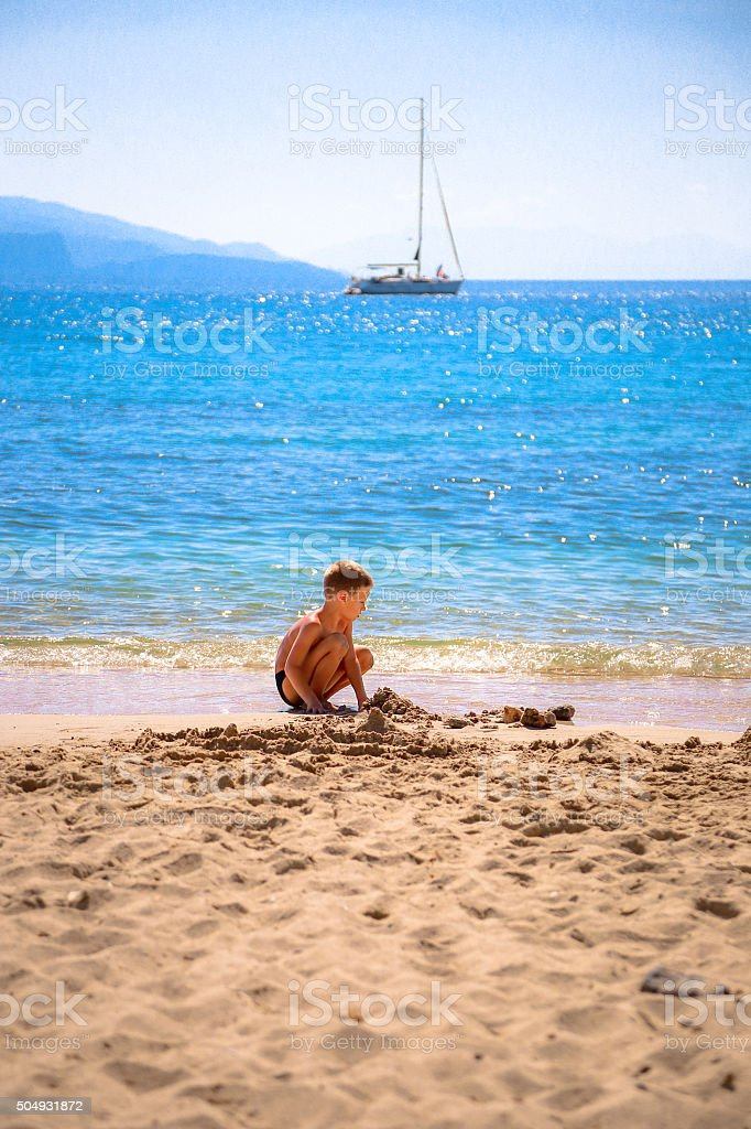Boy playing in sand on a beach, building sandcastles stock photo