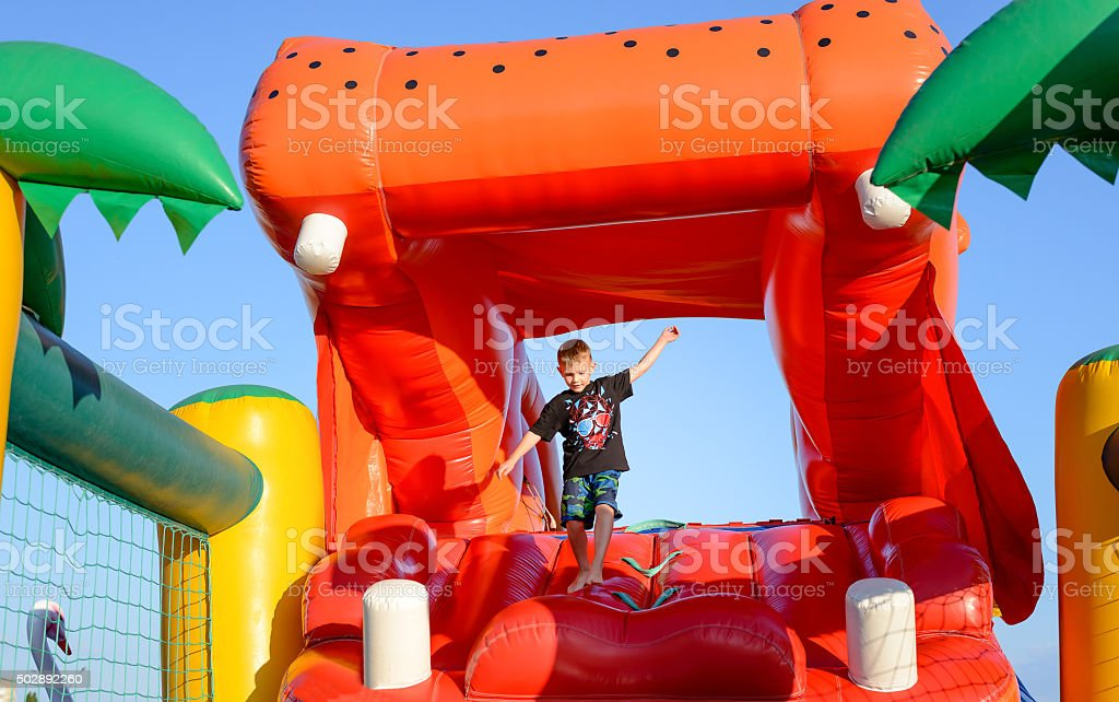 Boy Playing on Giant Red Inflatable Hippopotamus stock photo