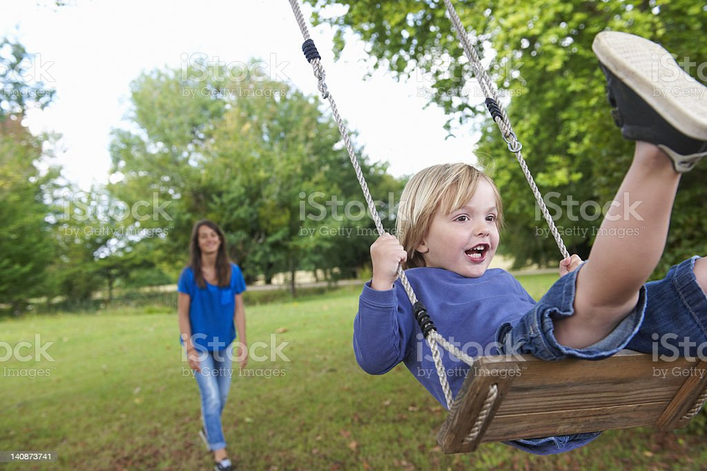 Boy playing on swing in backyard stock photo