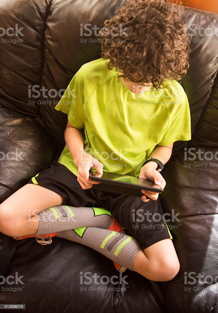 Boy Playing on Tablet stock photo