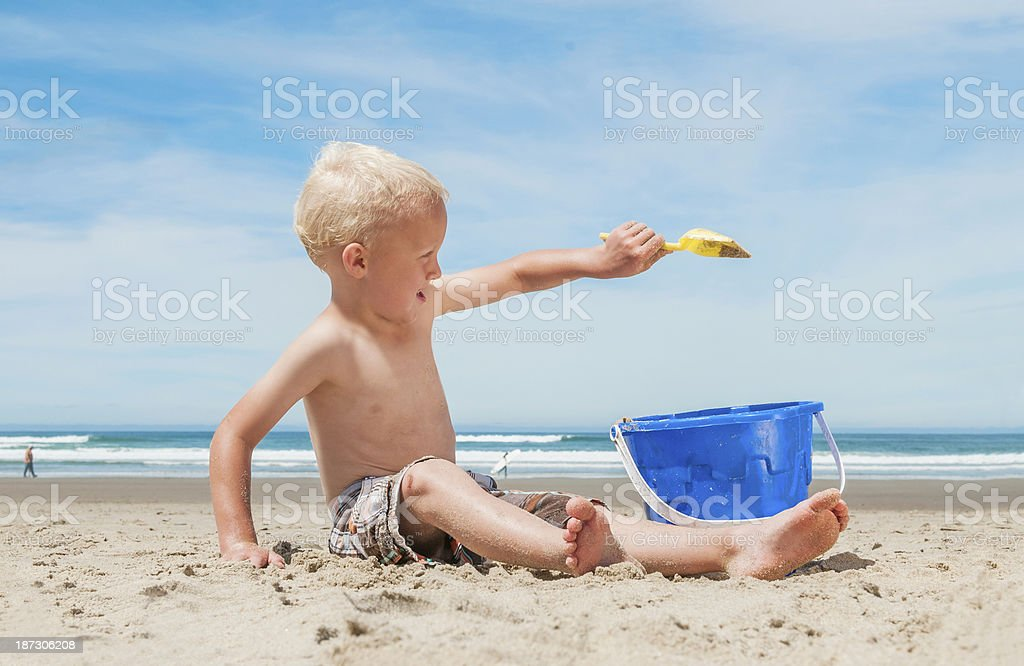 Boy playing on the beach with bucket. royalty-free stock photo