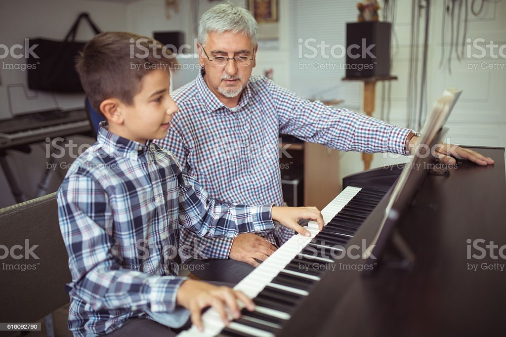 Boy playing piano on the class music stock photo