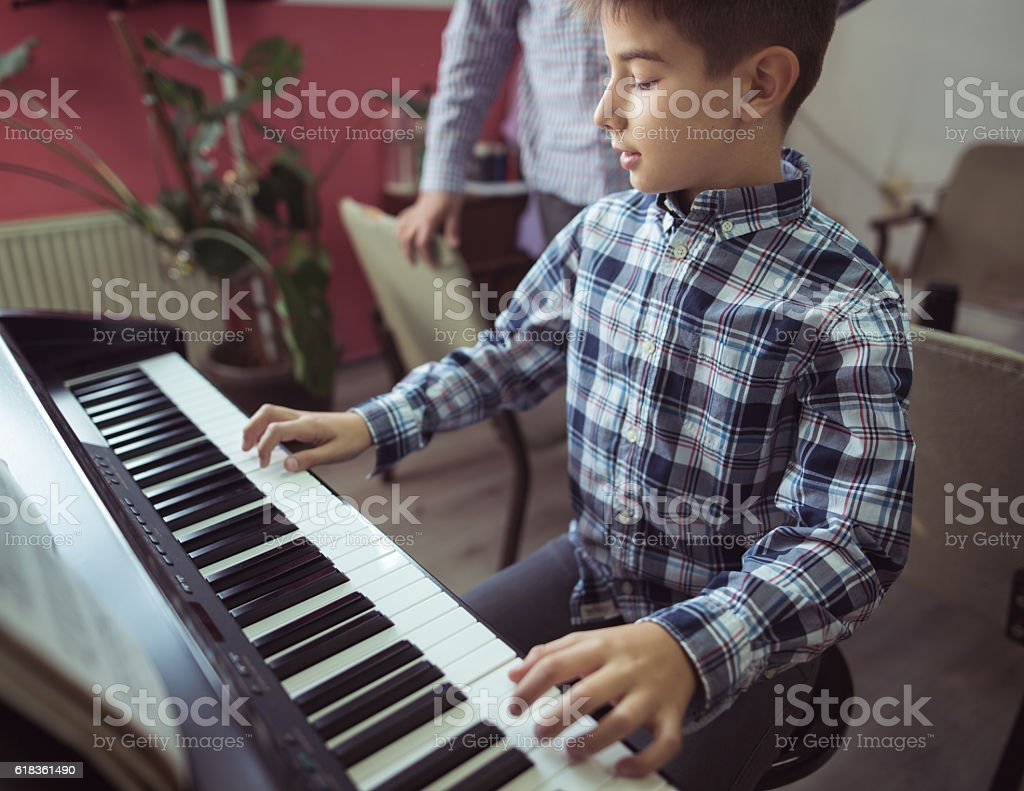 Boy playing piano stock photo