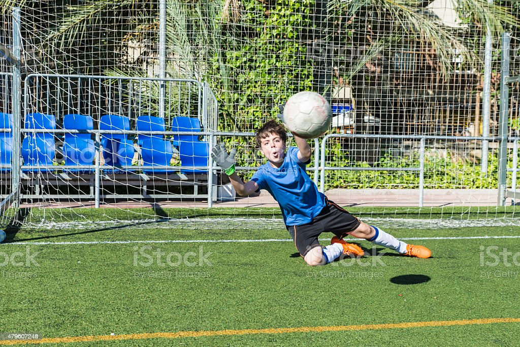 Boy playing soccer goalie stock photo