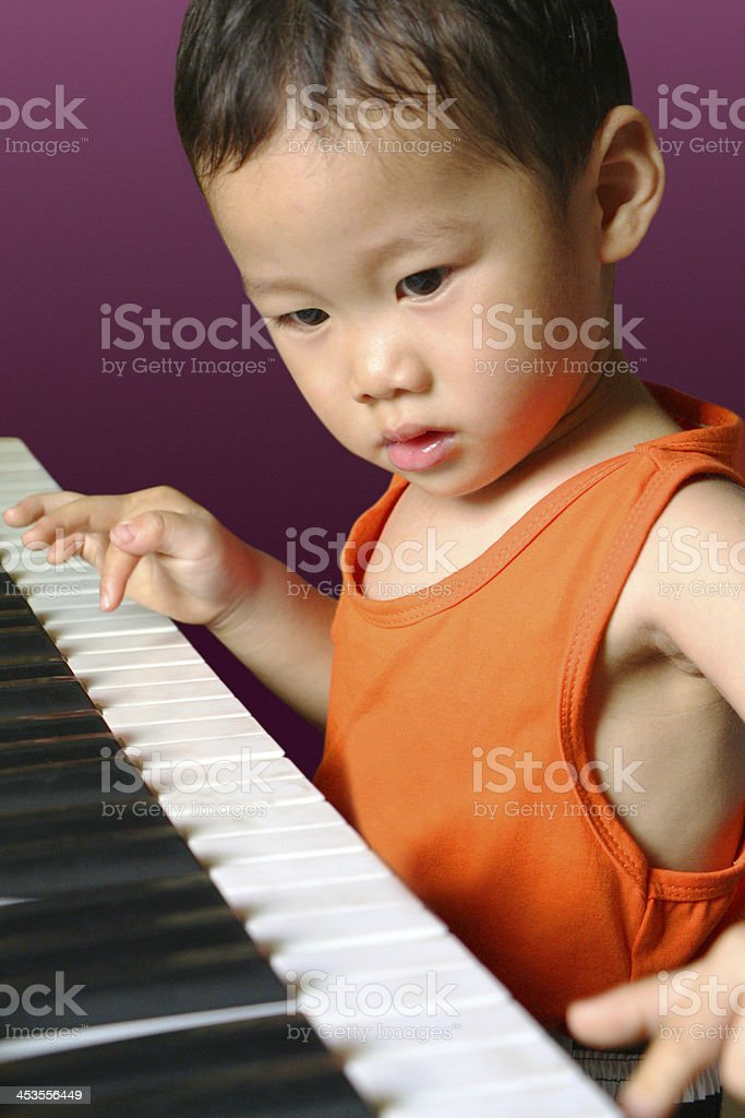 Boy playing the piano stock photo