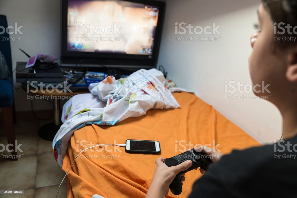 Boy playing video games at home stock photo