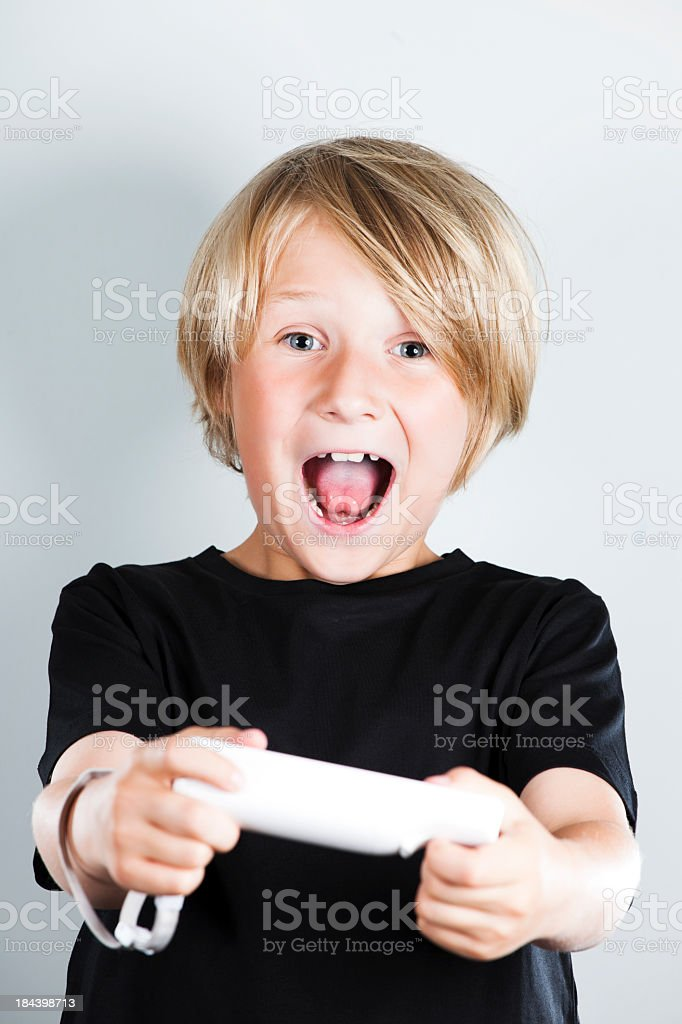 A boy playing video games with a wireless controller royalty-free stock photo