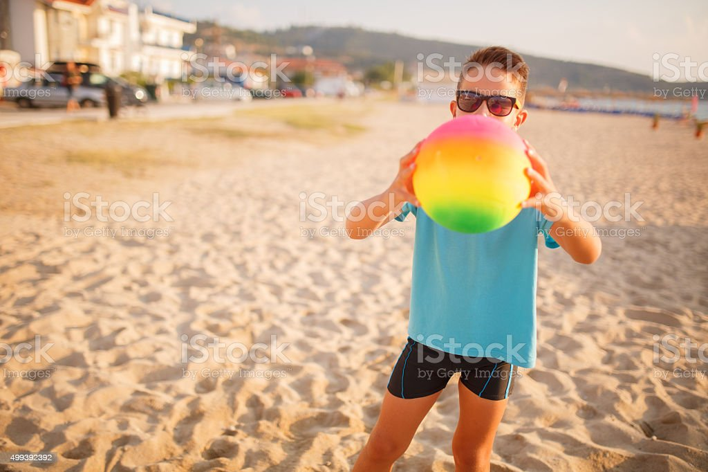 Boy playing volleyball on beach stock photo