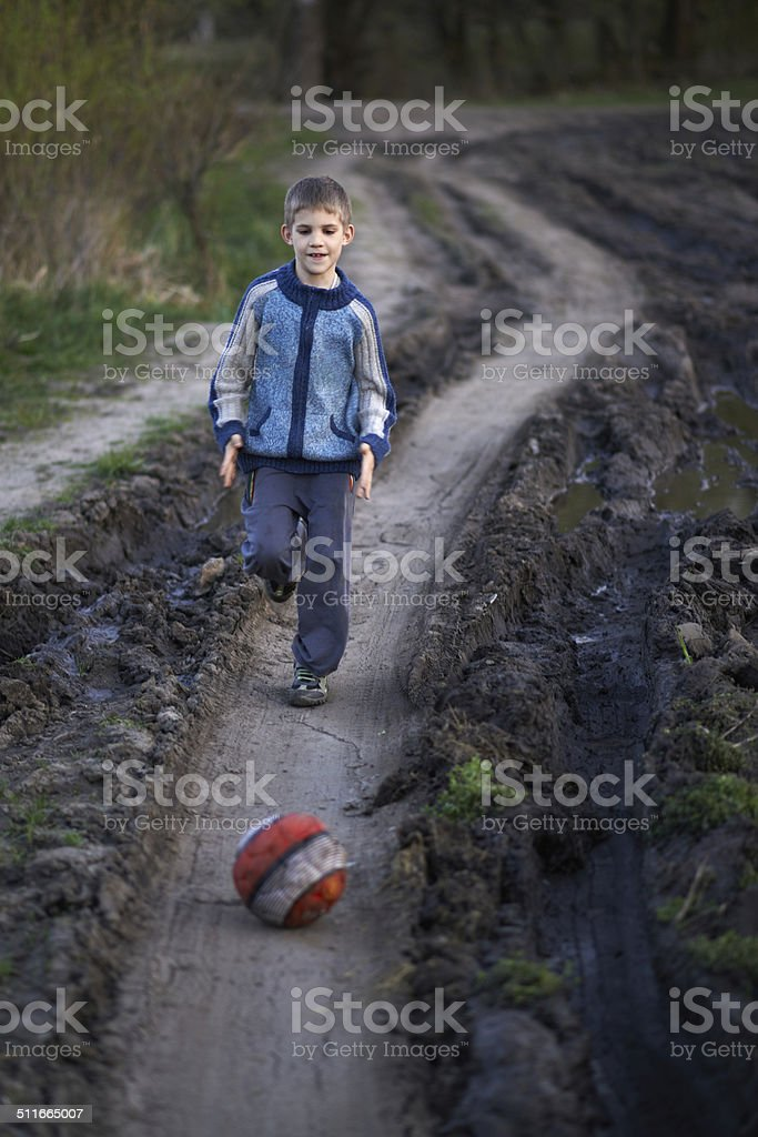 boy playing with a ball on the mud road stock photo