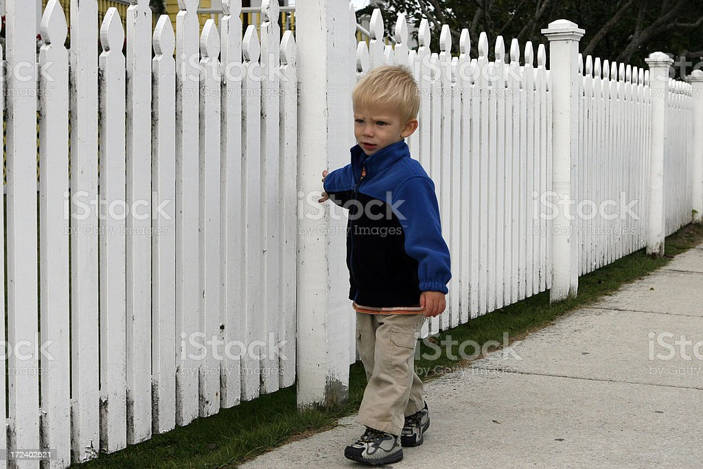 boy playing with a fence stock photo