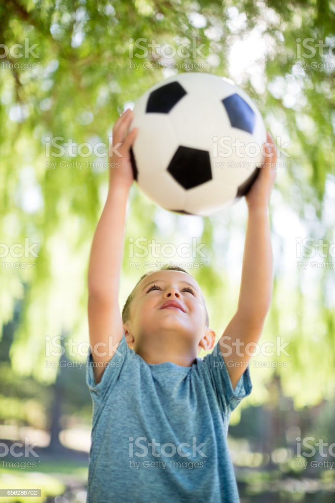 Boy playing with a football in park stock photo