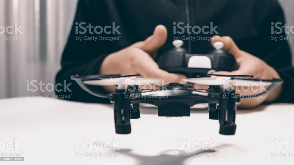 Boy Playing With A Small Quadrocopter Drone Close-up. stock photo