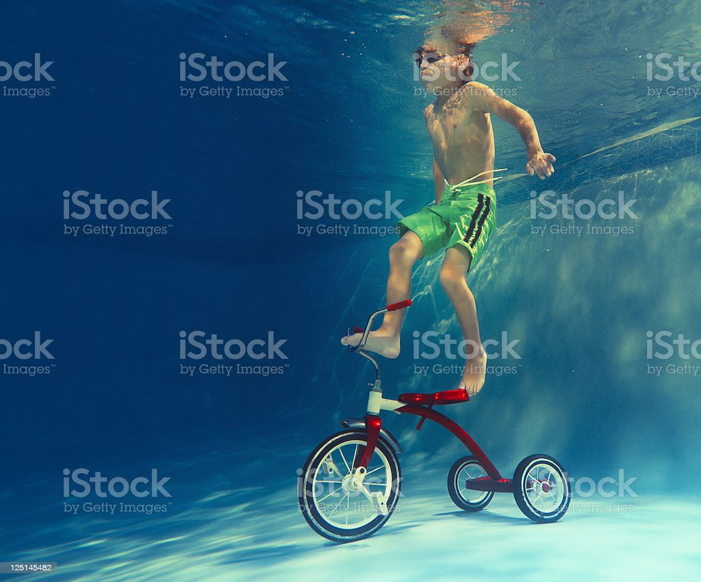 boy playing with a tricycle underwater stock photo