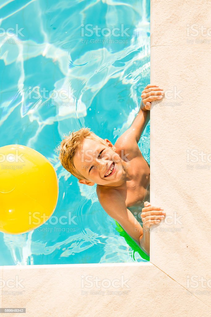 Boy (9 years) playing with beach ball in swimming pool stock photo