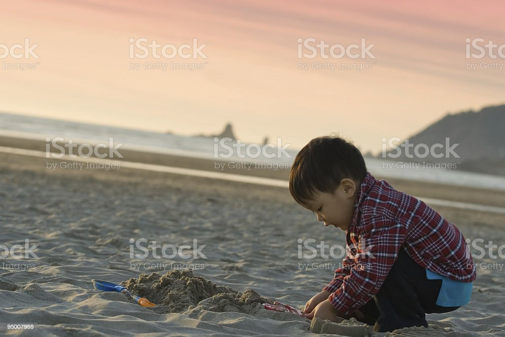 Boy Playing with Beach Sand stock photo