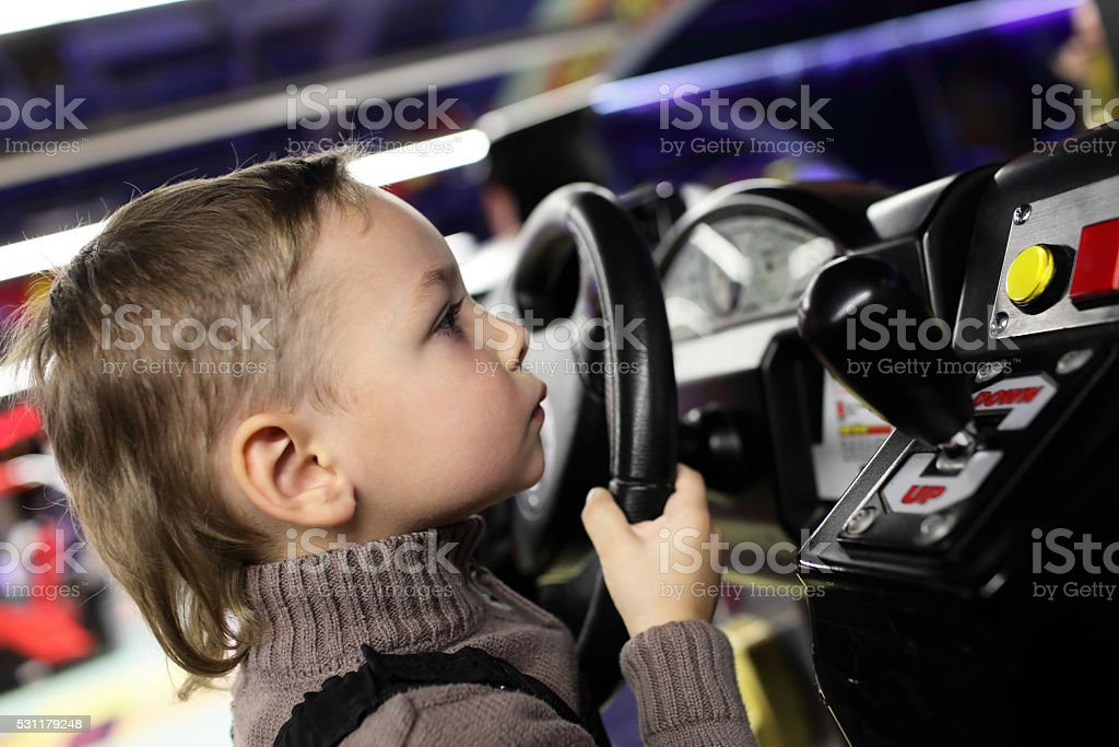 Boy playing with car simulator stock photo