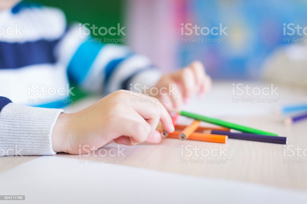 Boy playing with crayons close up shot stock photo