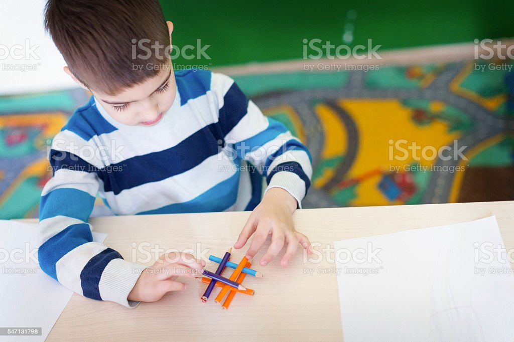 Boy playing with crayons in the class room stock photo