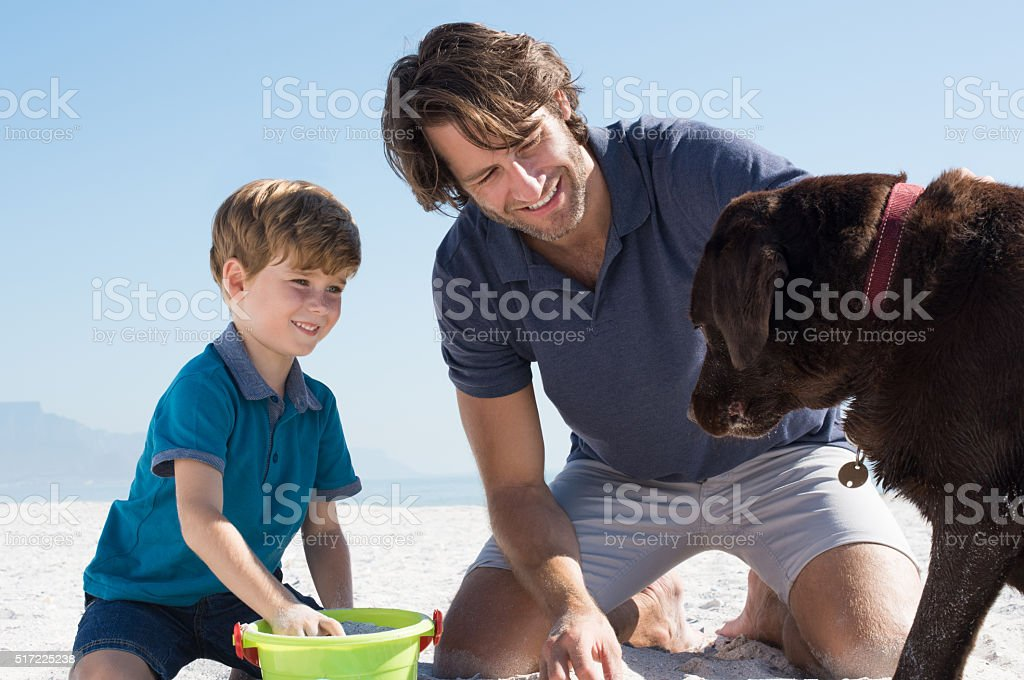 Boy playing with dad and dog stock photo