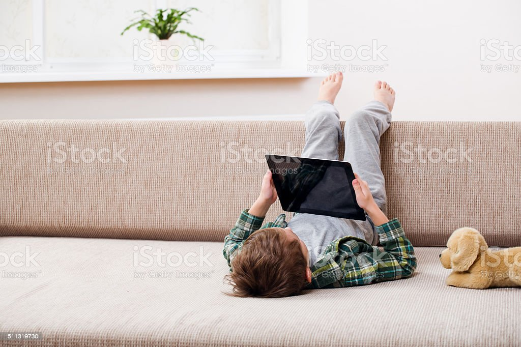 boy playing with digital tablet stock photo