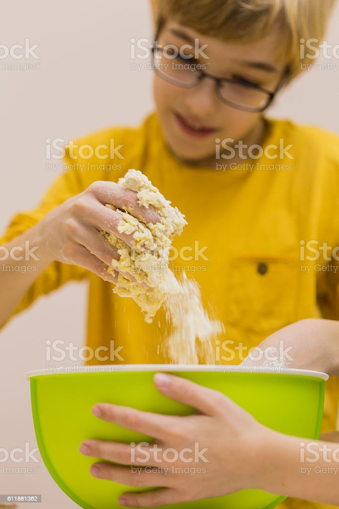 Boy playing with dough in the kitchen stock photo