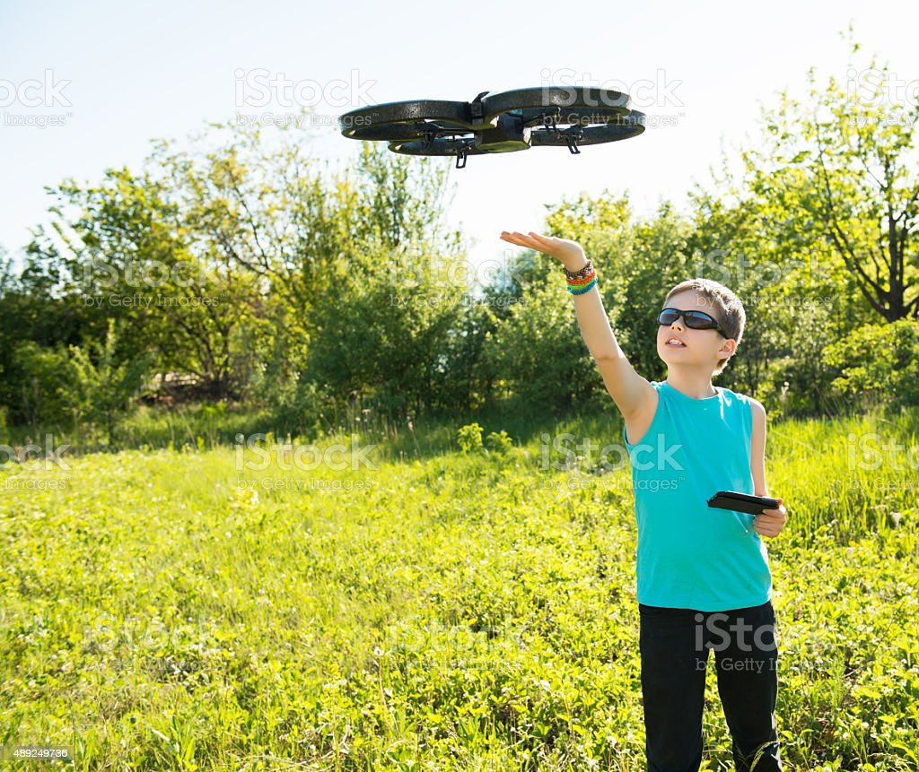 Boy playing with flying quadcopter with camera controlled by smartphone. stock photo