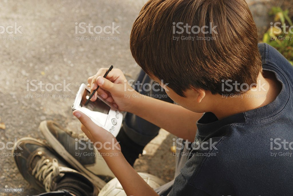 Boy playing with gadget royalty-free stock photo