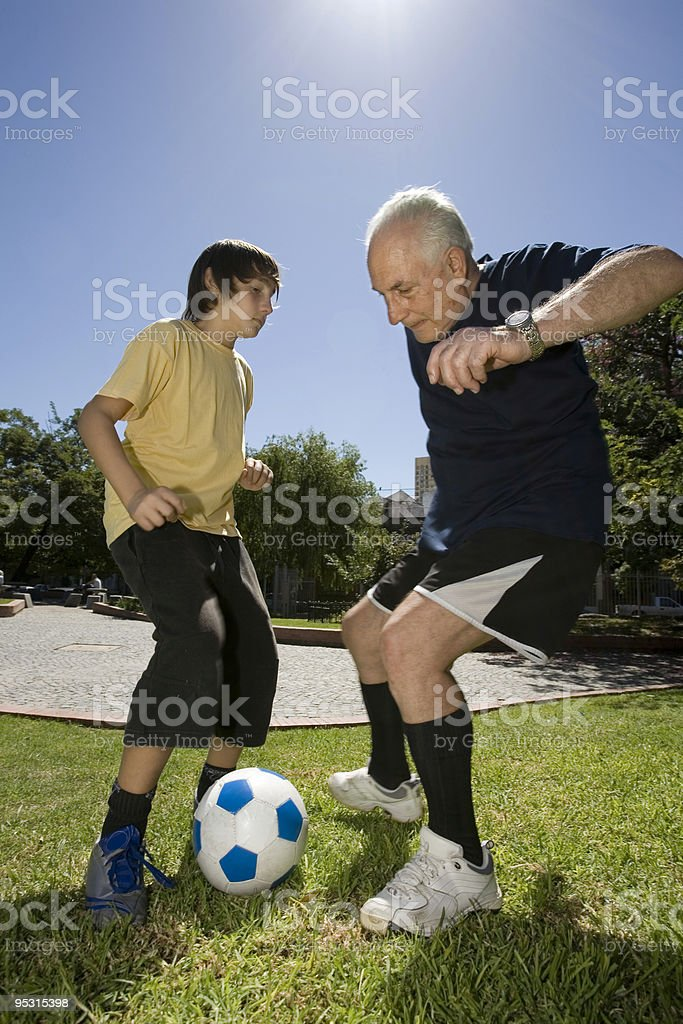Boy playing with his grandfather soccer royalty-free stock photo