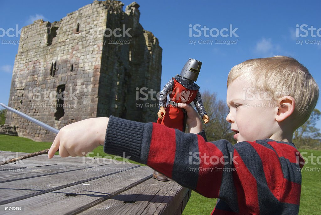 Boy playing with Knight at Etal Castle, Northumberland stock photo