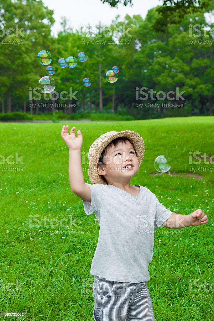 Boy playing with soap bubbles in the park stock photo